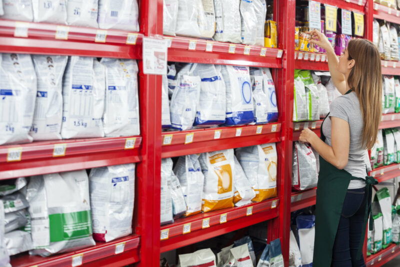 Side view of saleswoman arranging food packages on shelf in pet store